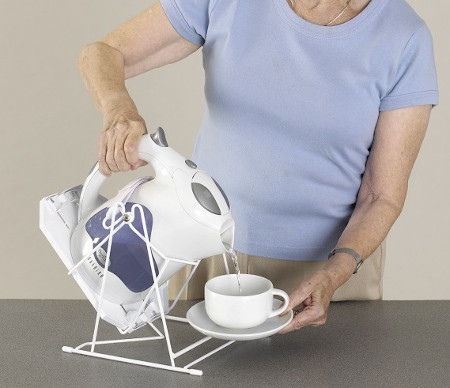 Elderly lady lifting a cup to the kettle tipper
